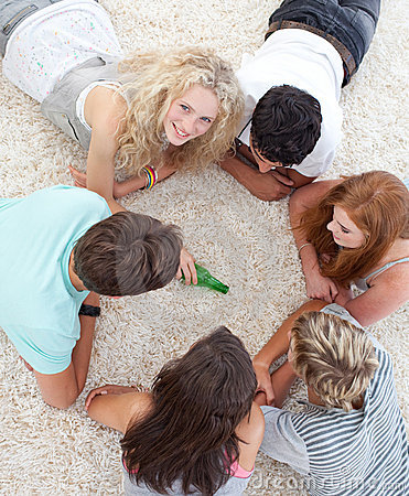 teenagers-playing-spin-the-bottle-on-the-floor-thumb12048194